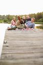 Group of friends relaxing on pier at lake - MASF05615
