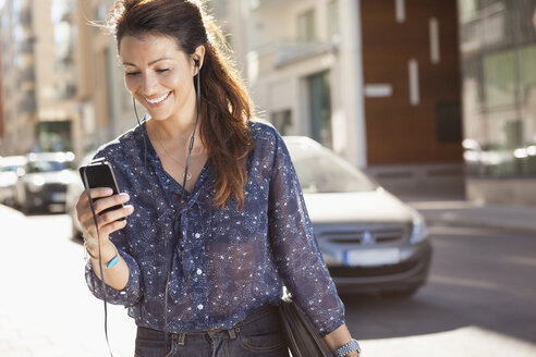 Happy businesswoman using mobile phone while listening music on street - MASF05618