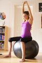 Full length of pregnant woman stretching on fitness ball at home - MASF05633