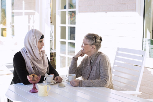 Female home caregiver and senior woman conversing while having coffee on porch - MASF05663