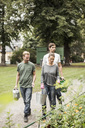 Friends with gardening equipment walking by garden - MASF05675