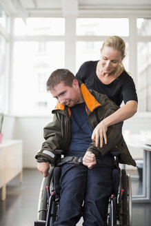 Female caretaker assisting disabled man on wheelchair at home - MASF05678