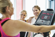 Friends looking at woman exercising on treadmill at gym - MASF05684