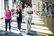 Friends conversing while walking at health club - MASF05687