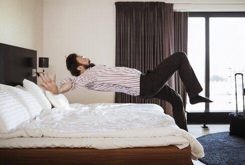 Full length of businessman jumping on bed in hotel room - MASF05690