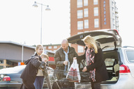 Family loading groceries in car trunk at parking lot - MASF05693