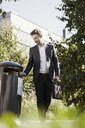 Businessman throwing garbage in bin at park - MASF05720