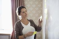 Businesswoman sticking memo notes on whiteboard - MASF05753