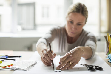 Businesswoman drawing line using ruler on paper - MASF05780