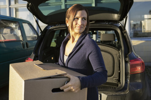 Businesswoman carrying cardboard box in front of car trunk - MASF05789