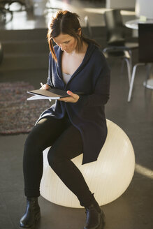 Businesswoman reading magazine while sitting on fitness ball in office - MASF05792