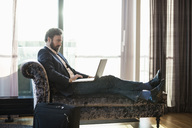 Businessman using laptop on chaise longue in hotel room - MASF05807