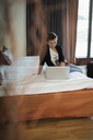Businesswoman using laptop on bed in hotel room - MASF05810