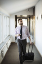 Businessman with suitcase walking in hotel corridor - MASF05813