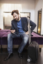 Businessman using mobile phone at hotel lobby - MASF05819