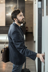 Businessman pushing button of elevator at hotel - MASF05822