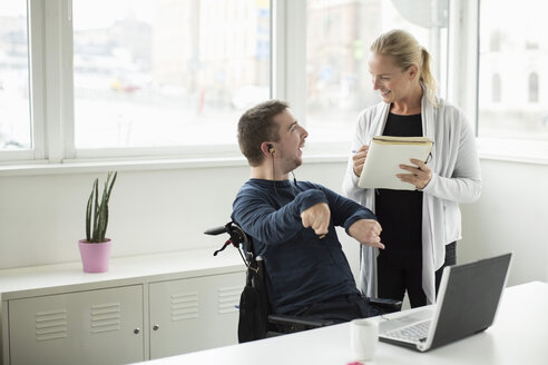 Disabled businessman discussing work with colleague in office - MASF05858