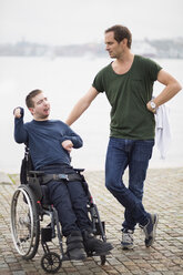 Disabled man on wheelchair taking with male caretaker by lake - MASF05861