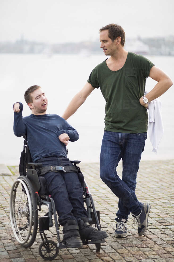 Disabled man on wheelchair taking with male caretaker by lake - MASF05861 - Maskot ./Westend61