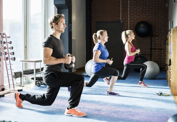 Customers exercising with kettlebells at gym - MASF05876