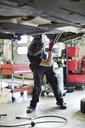 Young mechanic repairing car from below at auto repair shop - MASF05900