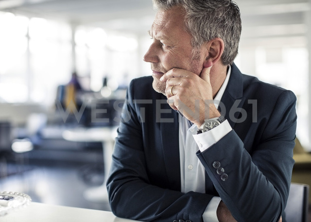 Thoughtful mature businessman looking away while sitting at desk in classroom - MASF05993