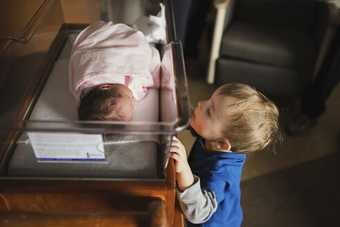 Brother looking at sister sleeping in crib at hospital - CAVF43466
