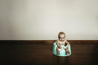 Baby girl with toy sitting on potty against wall at home - CAVF43475
