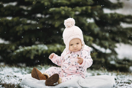 Baby girl sitting on blanket during snowfall - CAVF43484