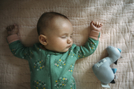 Overhead view of baby girl sleeping on bed at home - CAVF43487