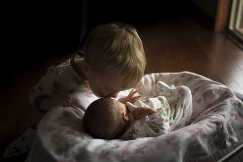 Brother kissing sister on forehead sleeping in moses basket at home - CAVF43490