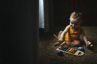 Baby girl playing xylophone on rug at home - CAVF43496