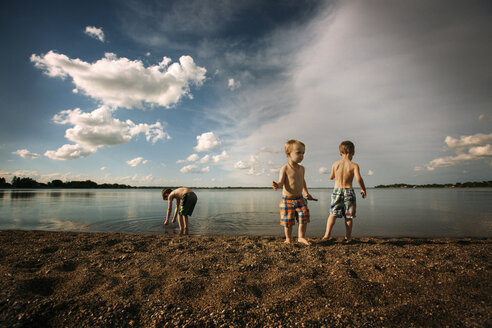 Brothers playing at lakeshore against cloudy sky - CAVF43502