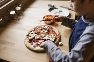High angle view of boy preparing pizza at home - CAVF43628