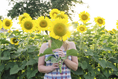 Woman hiding face with sunflower in farm - CAVF43664