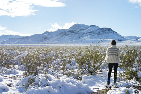 Young woman standing in field in winter with mountain in background - CAVF43736