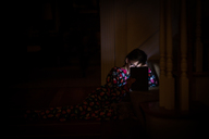 Girl using tablet computer in darkroom at home - CAVF43739