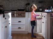Side view of girl sharpening pencil over garbage bin in kitchen - CAVF43745