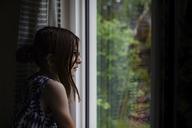 Thoughtful girl looking through window - CAVF43748