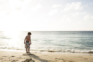 Rear view of shirtless boy standing at beach against sky on sunny day - CAVF43796