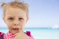 Close-up portrait of messy girl at beach against sky - CAVF43802