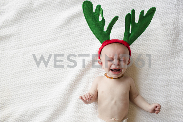 High angle view of cute baby boy in reindeer horns crying while lying on bed - CAVF43817