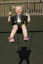 High angle view of cute girl swinging in playground during sunny day - CAVF43835