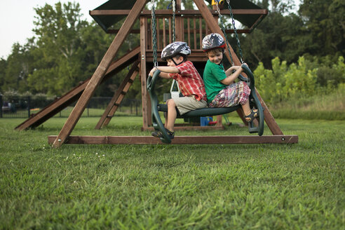 Playful brothers swinging in playground - CAVF43838