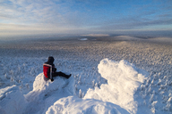 Hiker looking at view while sitting in snow covered mountain against sky - CAVF43859
