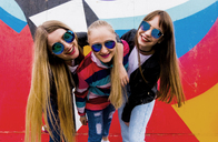 Portrait of happy female friends wearing sunglasses standing against graffiti wall - CAVF43880