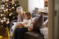 Grandmother assisting girl reading book while sitting on sofa at home - CAVF43976