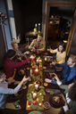 Friends toasting wine while enjoying meal during Christmas - CAVF44024