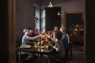 Friends toasting wine while having meal at table during Christmas - CAVF44030