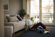 Full length of woman using laptop in living room at home - CAVF44057